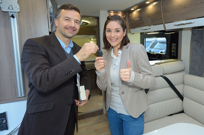 Two people exchanging keys to a new motorhome after passing thorough rv inspection services
