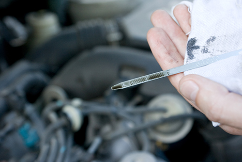 checking the engine oil while preforming rv inspection services